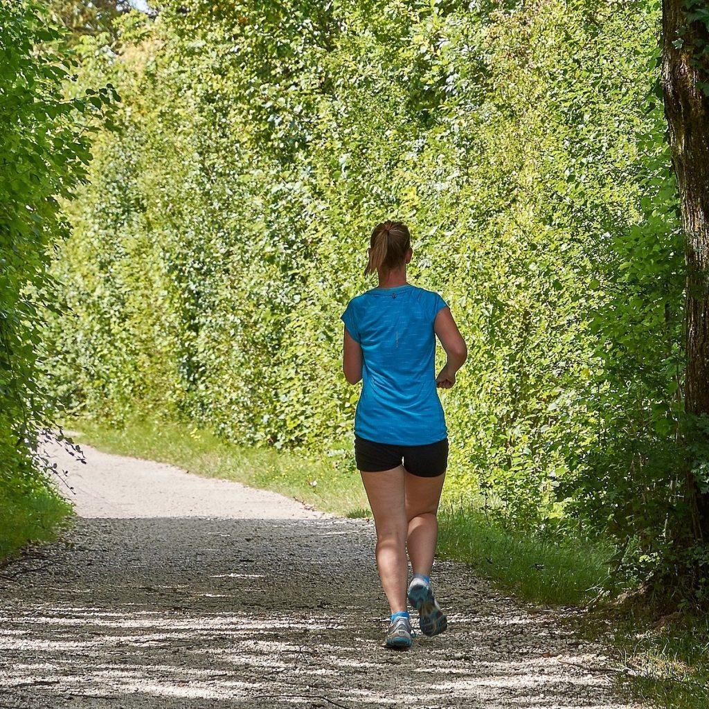 Kvinna i klimakteriet löptränar i skog