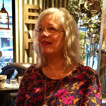 Kvinna i 50-årsåldern sitter på ett café