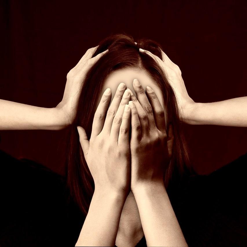 stressad kvinna håller händerna för ansiktet