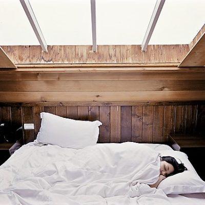 kvinna sover i säng med vitt täcke