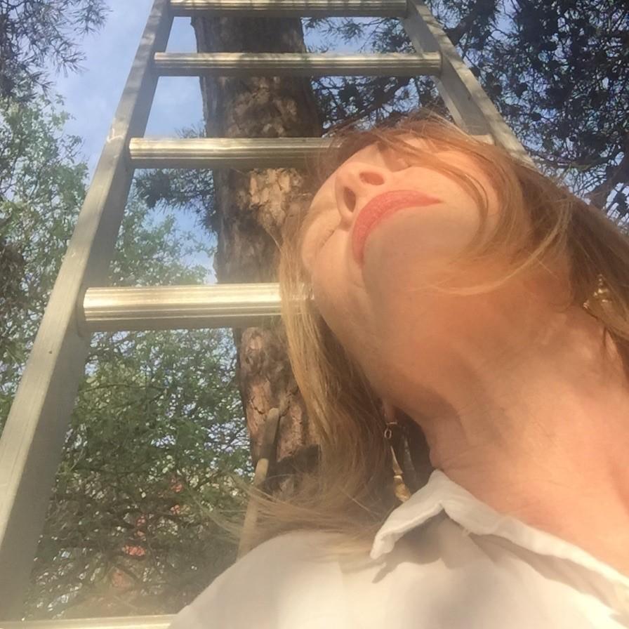 Medelålders kvinna med vallningar och stege i bakgrunden kisar mot solen