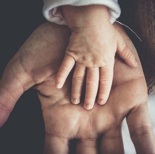 Ett litet barns hand i en vuxen hand, sorgen